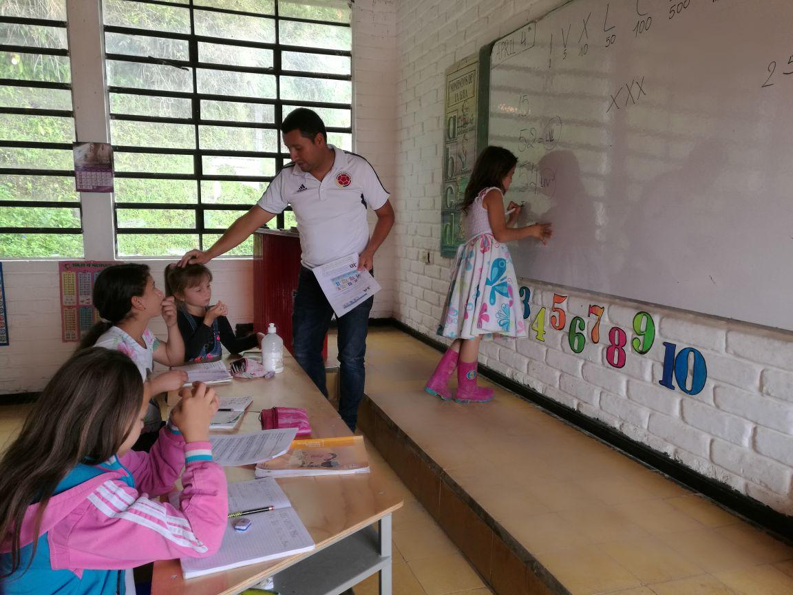 Cinco estudiantes hacen parte del programa Escuela Nueva en el que comparten con otras pequeñas de diferentes edades y reciben las instrucciones del mismo docente. Foto: Vanessa Sánchez.