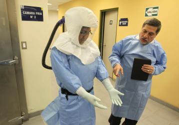 El Jefe del Instituto Nacional de Salud de Perú, Ernesto Bustamante (d), muestra los trajes utilizado para atender eventuales casos de ébola en el país / Foto: EFE/Paolo Aguilar