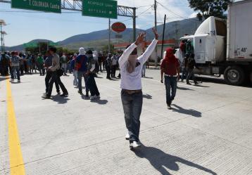 Fotografía del 23 de diciembre de 2014 que muestra a Integrantes de la CETEG bloqueando la caseta Chilpancingo-Acapulco para pedir apoyo a los conductores. Foto: EFE/José Méndez