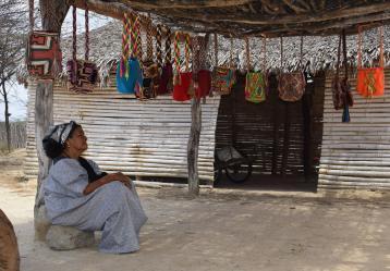 Mujer wayuu en su ranchería junto a su exhibición de mochilas. Foto: Miguel Ángel Cortés